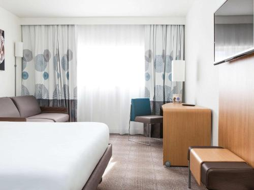A bed or beds in a room at Novotel Saint-Quentin en Yvelines