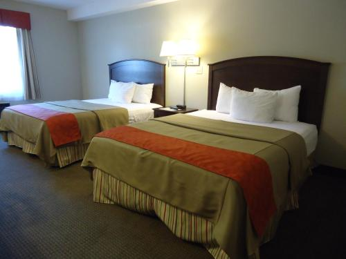 A bed or beds in a room at La Place Rendez-Vous Hotel