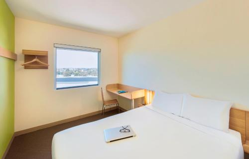 A bed or beds in a room at ibis Budget Sydney Olympic Park