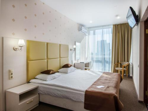 A bed or beds in a room at Sochi-Breeze Spa Hotel