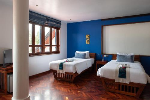 A bed or beds in a room at Indigo House Hotel