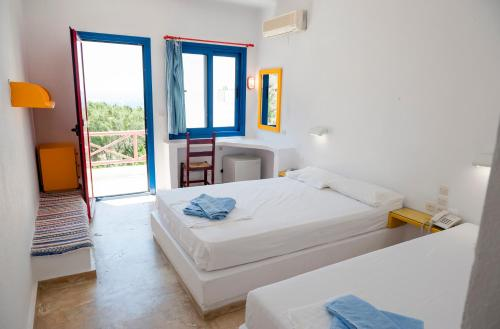 A bed or beds in a room at Plakias Bay Hotel