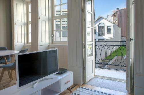 A television and/or entertainment center at MyStay Porto Bolhão - Pool & Garden