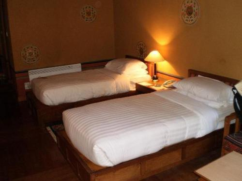 A bed or beds in a room at Olathang Hotel