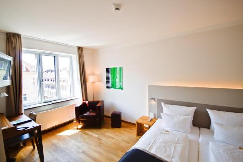 A bed or beds in a room at Qube Hotel Bergheim