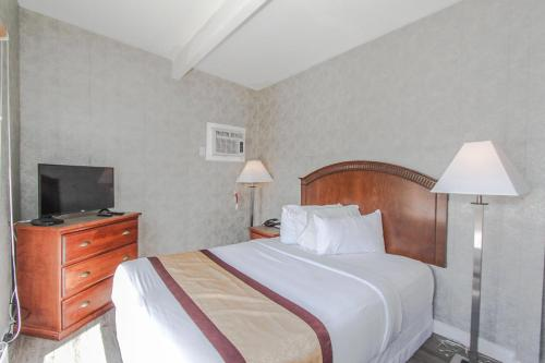 A bed or beds in a room at Canadas Best Value Inn Chinook Station
