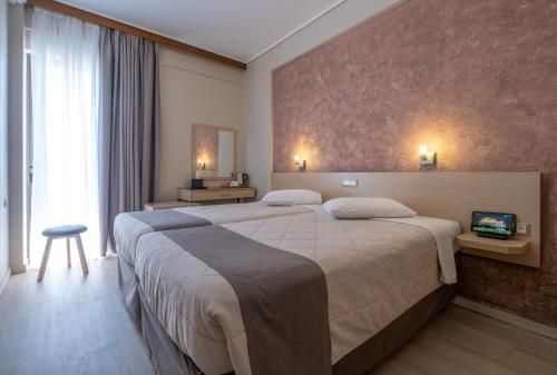 A bed or beds in a room at Acropolis View Hotel