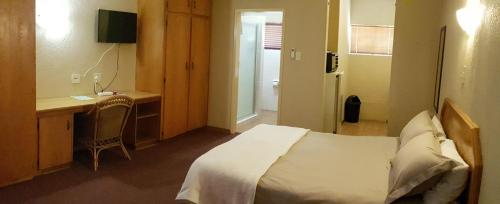 A bed or beds in a room at Pietersburg Lodge