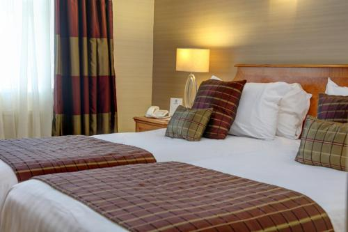 A bed or beds in a room at Best Western Aberavon Beach Hotel