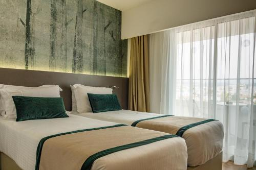 A bed or beds in a room at Pefkos City Hotel