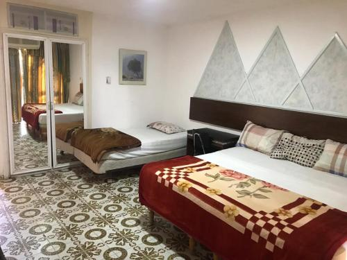 A bed or beds in a room at Aqaba Qazar Hotel