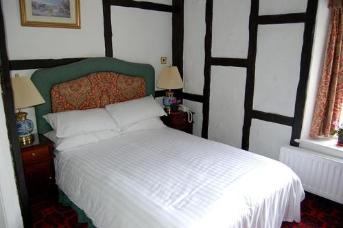 A bed or beds in a room at Dun Cow Inn