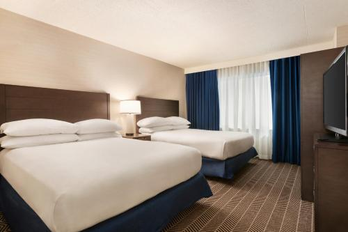 A bed or beds in a room at Embassy Suites Boston at Logan Airport