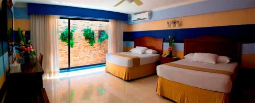 A bed or beds in a room at Hotel Plaza Colonial