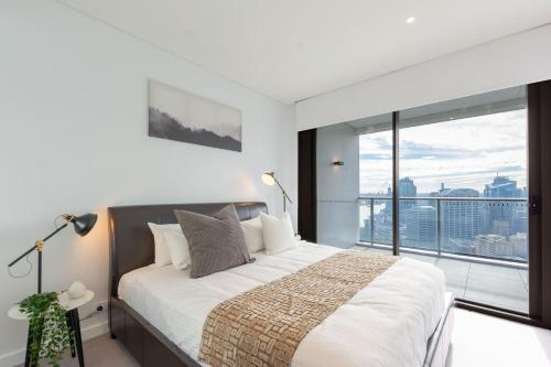 A bed or beds in a room at High Rise apt in Heart of Sydney wt Harbour View