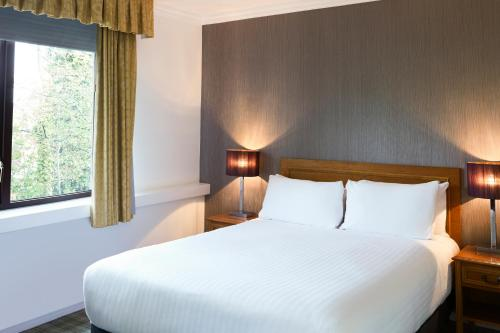 A bed or beds in a room at Mercure Sheffield Kenwood Hall & Spa
