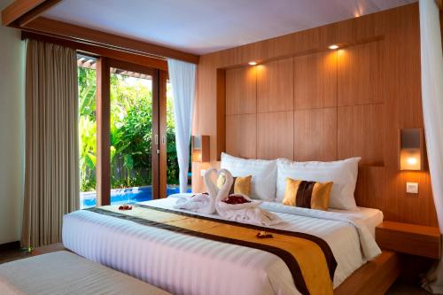 A bed or beds in a room at The Kings Villas & Spa Sanur