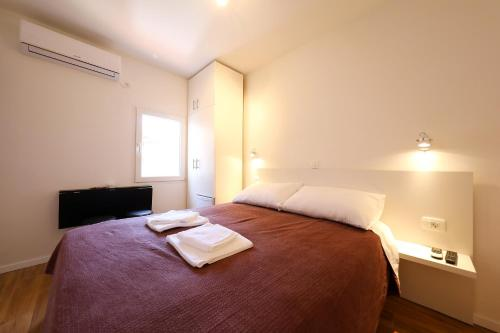 A bed or beds in a room at Pyrotima Apartments