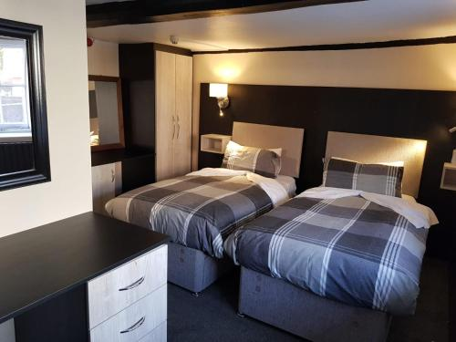 A bed or beds in a room at Old Black Horse Inn