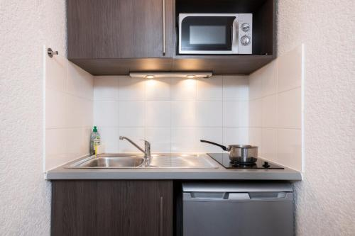 A kitchen or kitchenette at Aparthotel Adagio Access Strasbourg Petite France