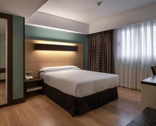 A bed or beds in a room at Hotel Ciudad de Logroño