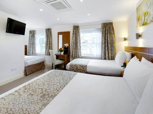 A bed or beds in a room at Park Avenue Bayswater Inn Hyde Park
