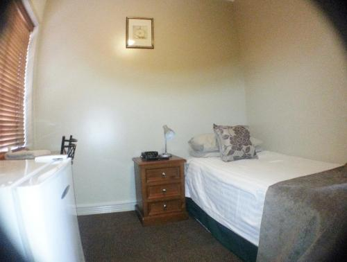 A bed or beds in a room at Ashfield Manor Sydney