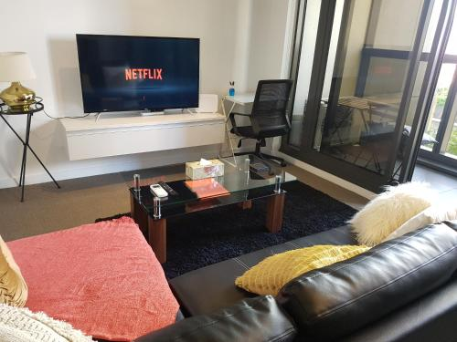 A television and/or entertainment center at Melbourne CBD Views-Free Parking Wine Wifi Netflix