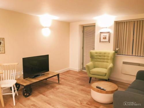 A television and/or entertainment center at Homely Serviced Apartments - Figtree