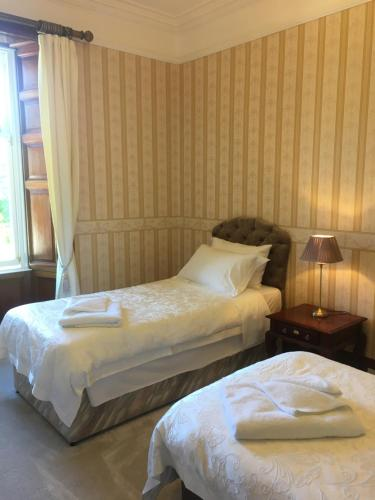 A bed or beds in a room at Ledgowan Lodge Hotel