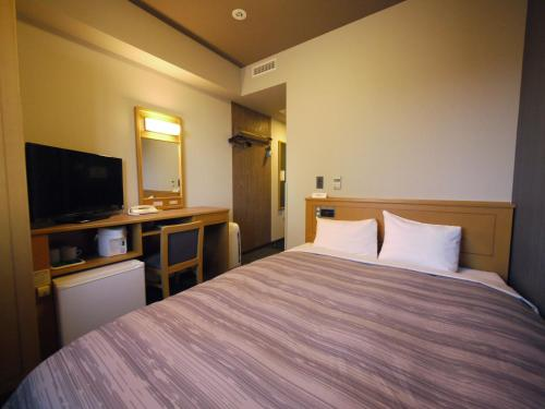 A bed or beds in a room at Hotel Route-Inn Sapporo Kitayojo