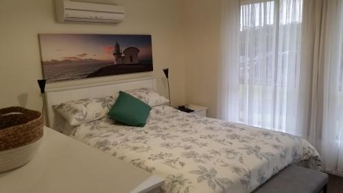 A bed or beds in a room at Twin Palms Holiday House at Lighthouse