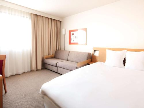 A bed or beds in a room at Novotel Atria Nimes Centre