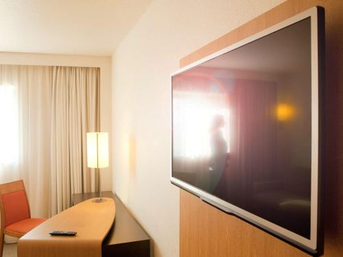 A television and/or entertainment center at Novotel Atria Nimes Centre