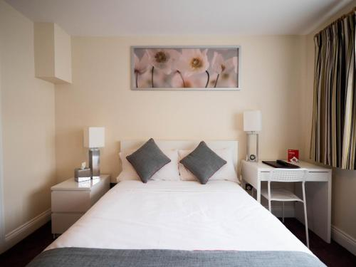 A bed or beds in a room at OYO The Dakota Baginton