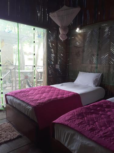Ein Bett oder Betten in einem Zimmer der Unterkunft Jungle Hut Bungalow