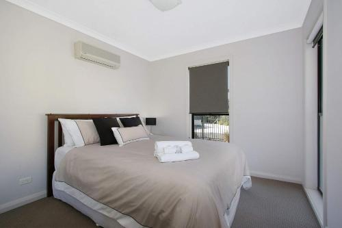 A bed or beds in a room at Cypress Townhouse 23 - Mulwala