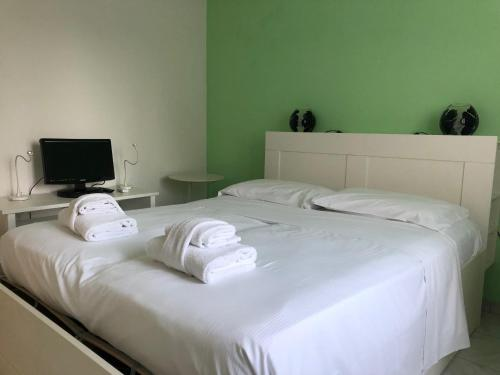 A bed or beds in a room at HomeatHotel - Bilo Alcuino Apt.