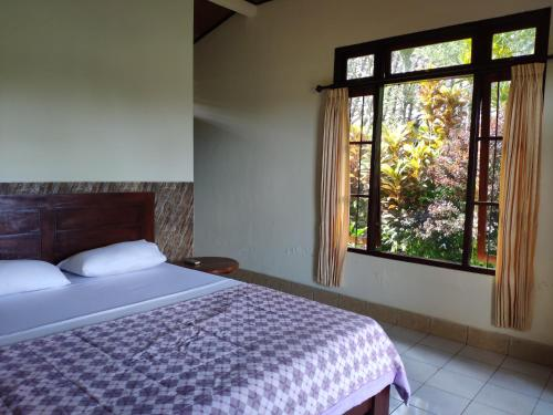 A bed or beds in a room at Rijasa Homestay