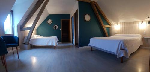 A bed or beds in a room at Le Champ du Pré