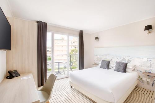 A bed or beds in a room at Best Western Plus Antibes Riviera