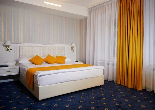 A bed or beds in a room at Belvedere Nevsky Business Hotel