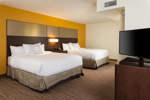 A bed or beds in a room at Residence Inn by Marriott Kansas City at The Legends