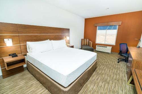 A bed or beds in a room at Holiday Inn Express & Suites Las Vegas SW Springvalley