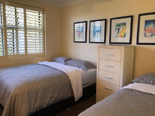 A bed or beds in a room at Frangipani Beachfront Lodge 208 on Hamilton Island by HamoRent