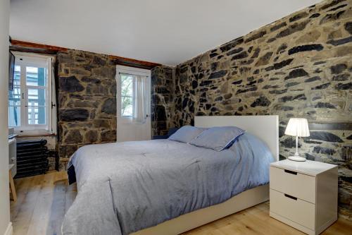 A bed or beds in a room at Hôtel Maison Ste-Ursule
