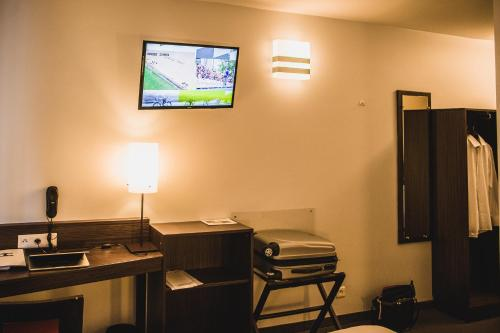 A television and/or entertainment centre at DC Hotel & Restaurant Charleroi Airport