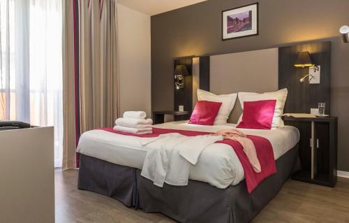 A bed or beds in a room at Odalys City Colmar La Rose d'Argent