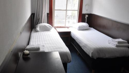 A bed or beds in a room at Budget Hotel Marnix City Centre