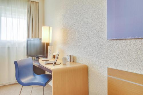 A television and/or entertainment center at Novotel Poissy Orgeval
